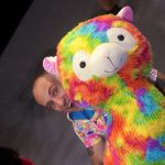 A shaven-headed person with a giant multi-coloured alpaca